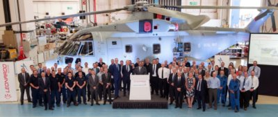 A group of people stand in front of a Merlin Mk2 helicopter